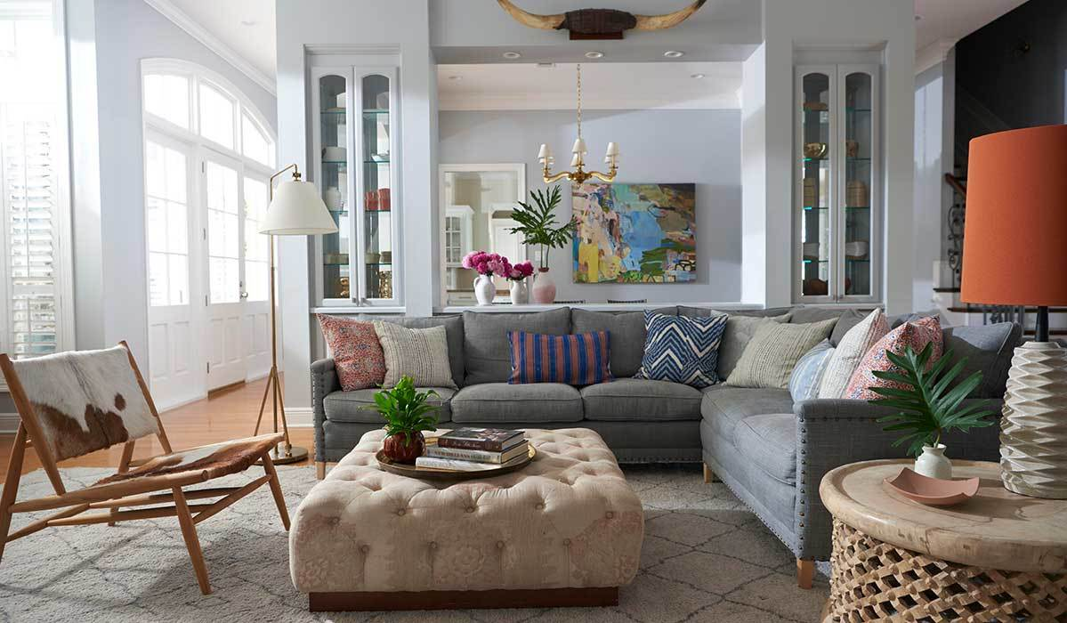 Living room with a gray sectional, accent chair, upholstered ottoman, and more. photo