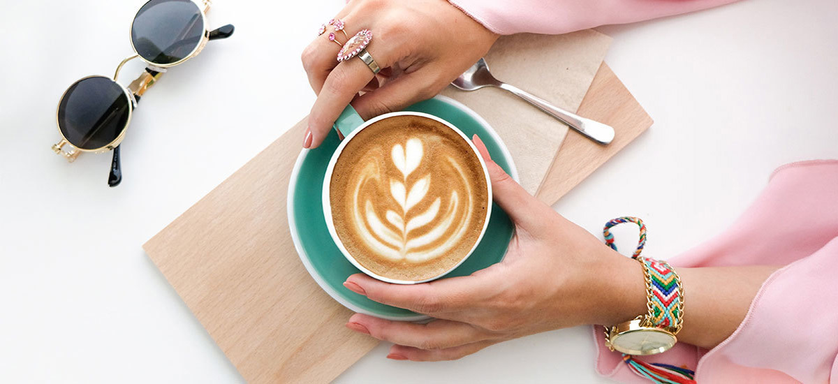 Woman holding latte with foam