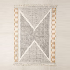 Neutral rug with a geometric pattern and fringed detailing photo