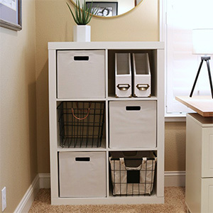 White shelving unit with baskets for organization. photo