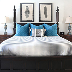 Black post bed with striped bedding. photo