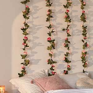 Four strands of rose vine garland hanging in a white bedroom behind a pile of pillows from Urban Outfitters photo