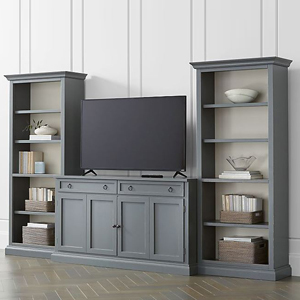 Slate gray entertainment center with two bookshelves on the sides filled with small decor photo