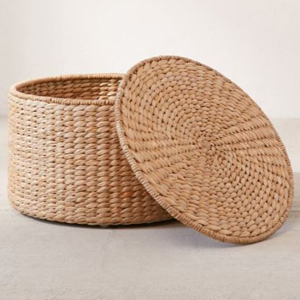 Round rattan storage ottoman with the lid set up against the bin photo
