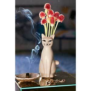 Tall, thin white cat-shaped vase with red flowers inside photo