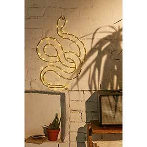 Yellow light sculpture in the shape of a snake against a brick wall photo