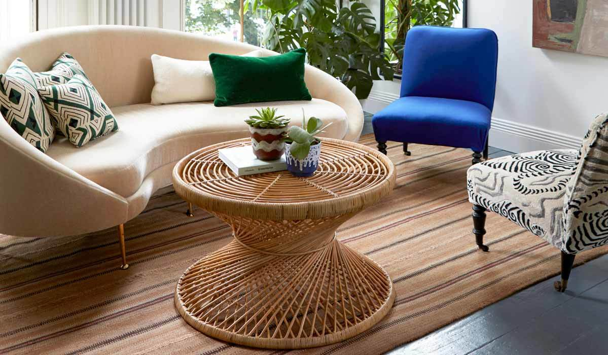 Living room featuring a curved ivory sofa, two accent chairs, and a rattan coffee table photo