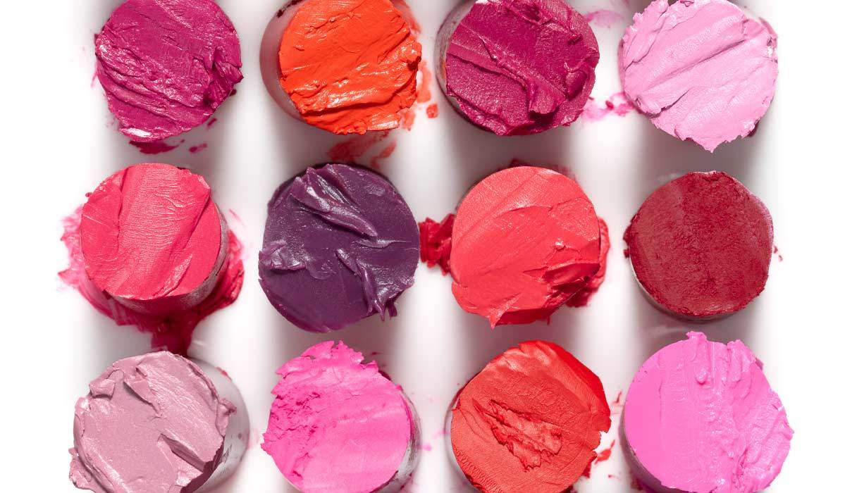 Lipstick in 12 different shades of red, purple, and pink photo