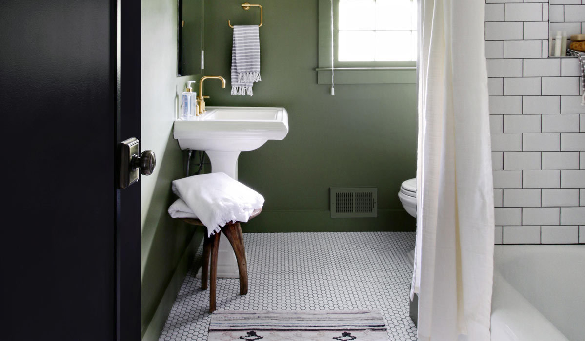 Modern bathroom with white tiles, gold hardware, and green walls photo