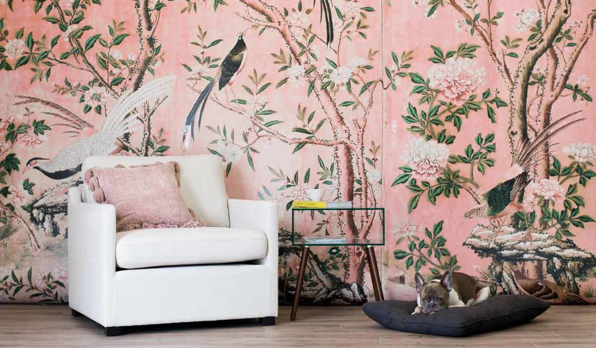 A room featuring pink wallpaper with birds, floral, and trees on it photo