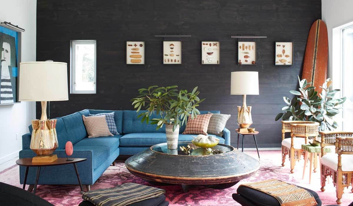 Living room featuring a dark shiplap wall, a blue sofa, a pink rug, and more photo