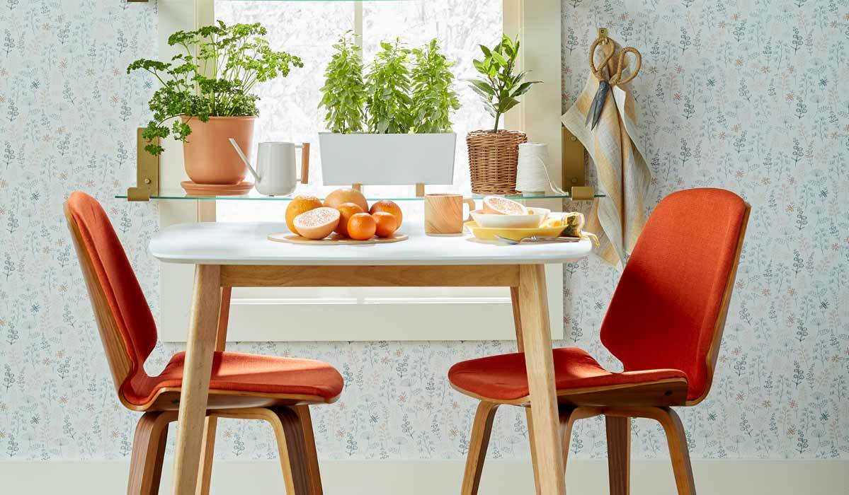 Midcentury-modern dining table with two orange dining chairs. photo