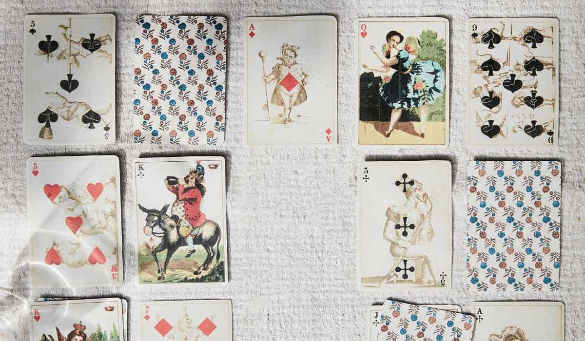 A deck of vintage playing cards laid out on white carpet photo