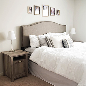Gray bed frame with white bedding. photo