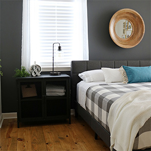 Dark gray bedroom with buffalo check bedspread and black accent table. photo