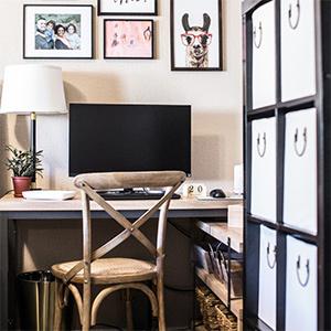 Black desk with a computer and a gallery wall of photos above. photo