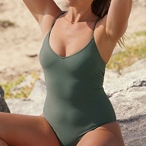 A woman wears an olive green strappy one-piece swimsuit while at the beach photo