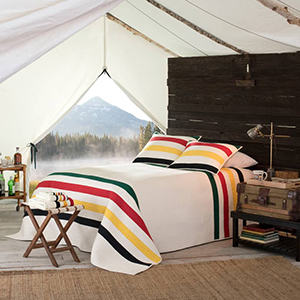 White, green, red, yellow, and black striped Pendleton quilt in a tent from Nordstrom photo