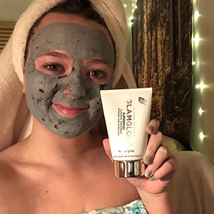 A photo of the writer wearing the Glamglow Supermud acne-clearing face mask with a shower towel on her head photo