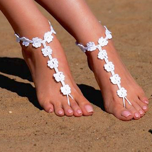 White barefoot sandals featuring crocheted flowers photo