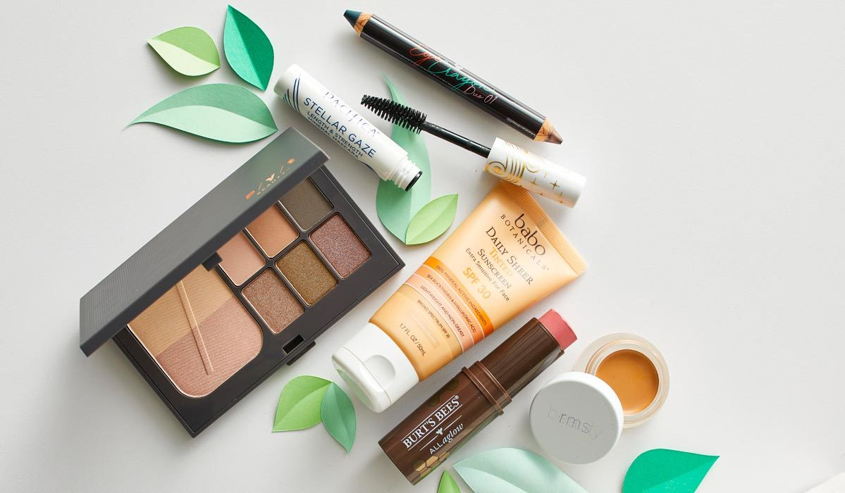 An assortment of natural makeup, including mascara, eyeshadow palette, lip and cheek stick, and mineral sunscreen photo