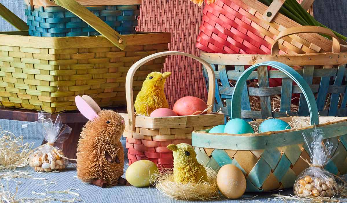 Colorful chipwood Easter baskets with dyed eggs and rabbit and baby chick figurines. photo