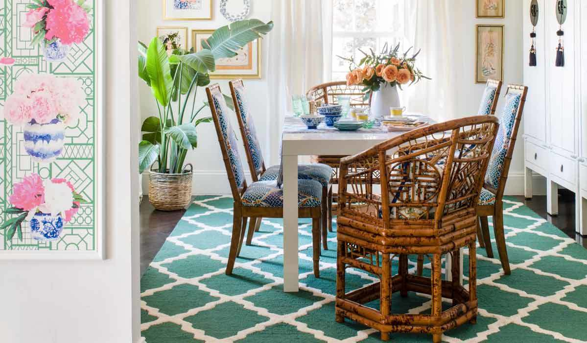 Dining room featuring a bright teal rug, a plant, and unique wood chairs photo