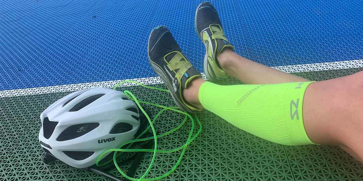 Girl stretching and wearing neon green leg compression sleeves photo