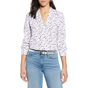 A woman wears a white, black, and lilac blouse with jeans photo
