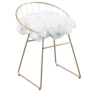 Desk chair made with a rose gold frame and white sheepskin photo