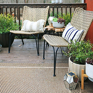 Two wicker chairs decorated with throw pillows photo
