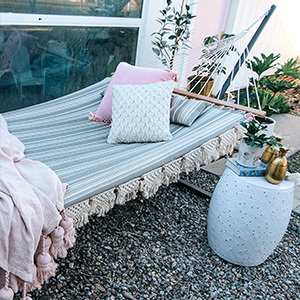 Striped hammock and throw pillows with a side table photo