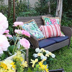 Wicker loveseat with blue cushions and floral pillows photo