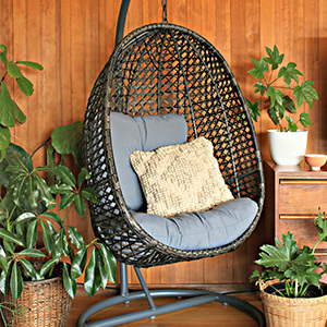 Brown wicker egg chair with a stand photo