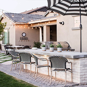 Black and white bar chairs with an umbrella and string lights photo
