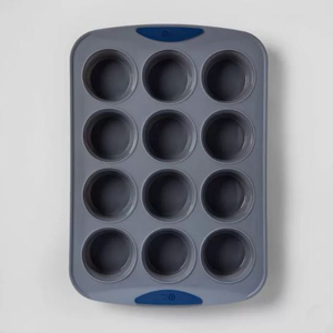 Black silicone muffin pan with 12 slots with blue accent handles photo