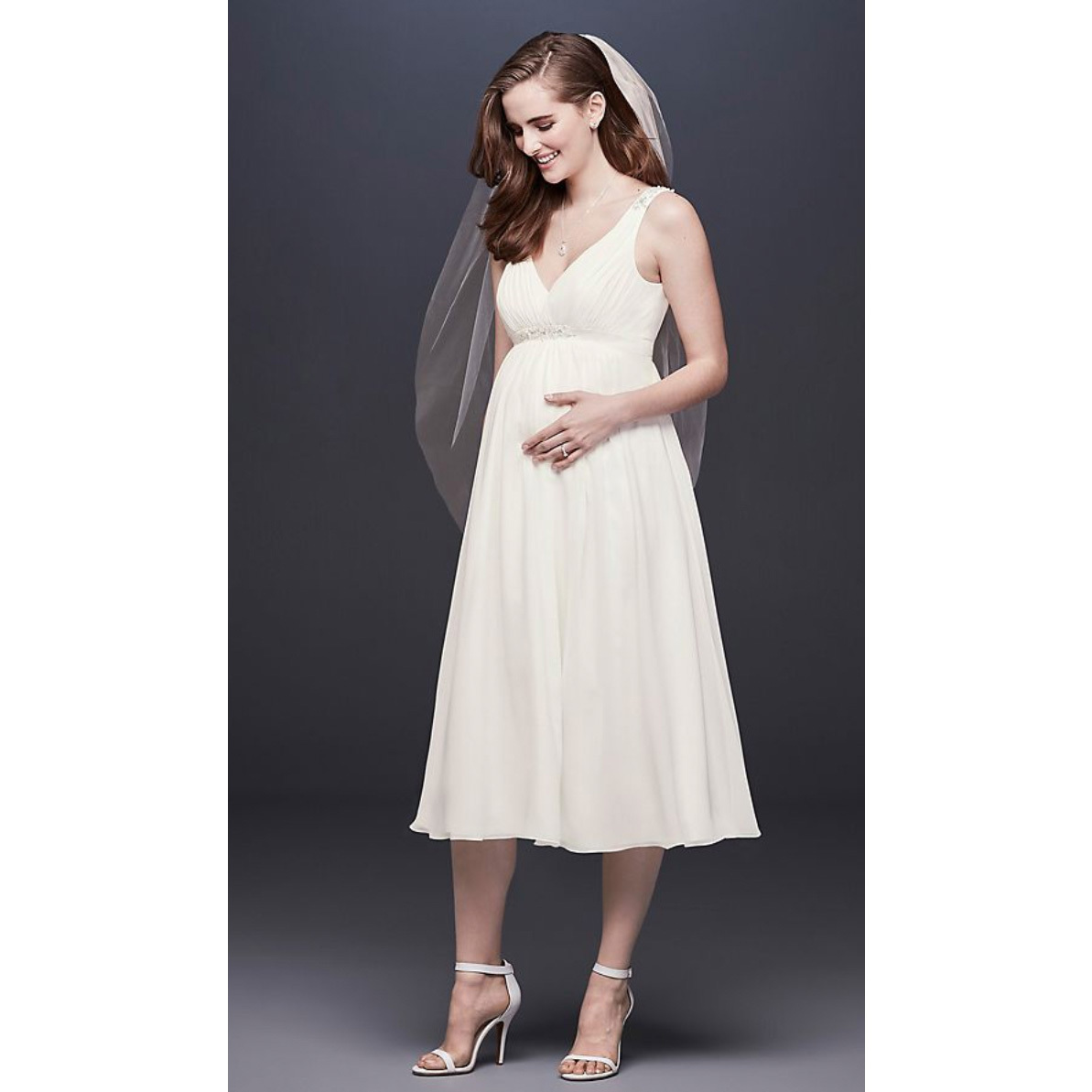 Model posing in David's Bridal Collection Chiffon V-Neck Tea-Length Maternity Wedding Dress photo
