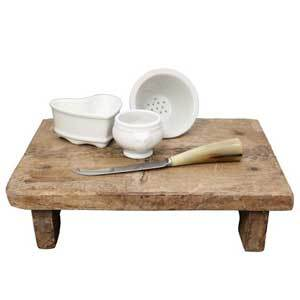 A wooden footed cutting board featuring a cheese knife, heart-shaped strainer, round strainer, and small bowl photo