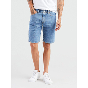 Man wearing a pair of Levi's jean shorts with a white t-shirt and white sneakers. photo