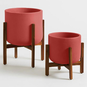 two red ceramic planters on wooden plant stands photo
