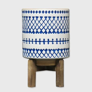 white planter with blue geometric design on a wooden plant stand photo