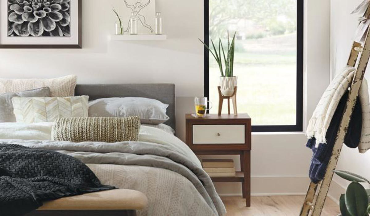 Modern bedroom featuring neutral bedding and decor