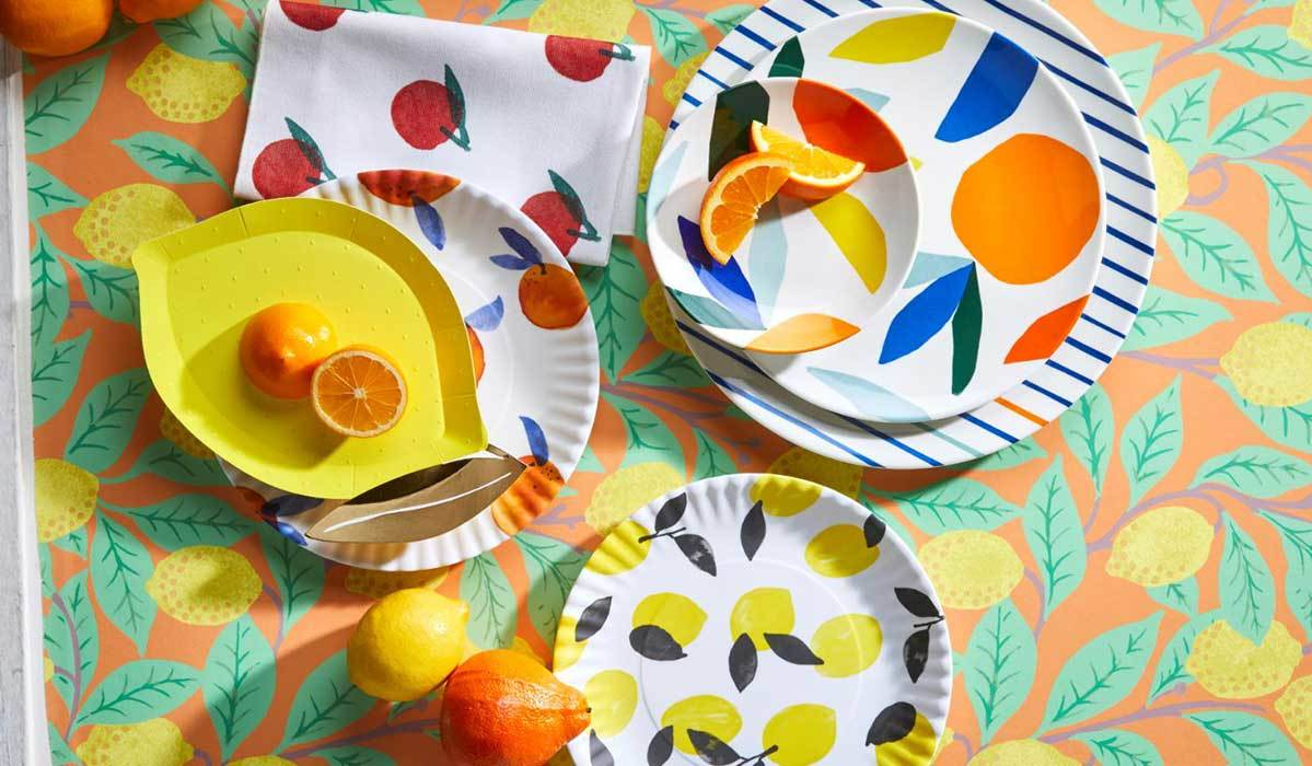 Lemon tablecloth with colorful plates and fruits photo