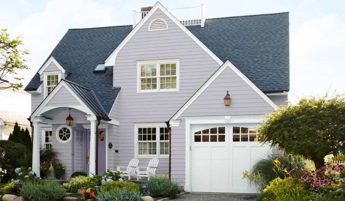 A lavender house with an attached garage and two white chairs on the porch photo
