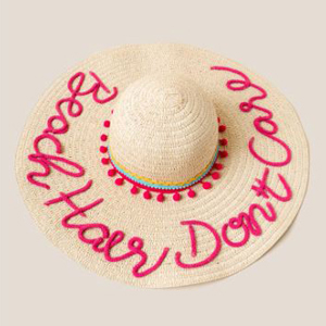 Straw hat with pink, blue, and yellow decoration and pink wording that says beach hair don't care photo