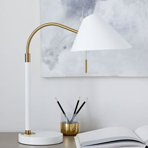 white mid-century style desk lamp on a desk with a notebook and pencil cup photo