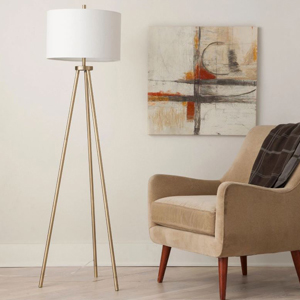 brass tripod floor lamp with white shade next to an accent chair with blanket and wall art photo