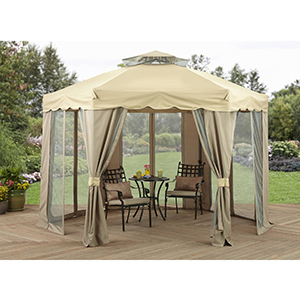 Large tan gazebo with two chairs and a small round table inside it photo