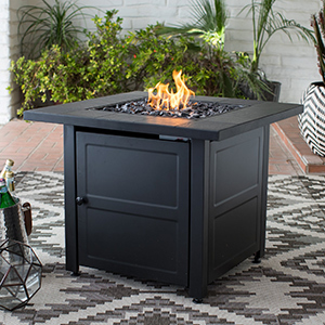 Black outdoor fire table with a pattern rug beneath it photo