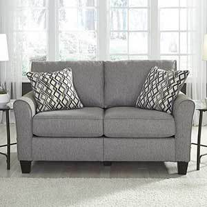 Gray love seat with two printed pillows photo